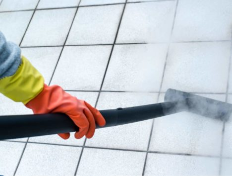 woman cleaning the bathroom with a steam cleaner