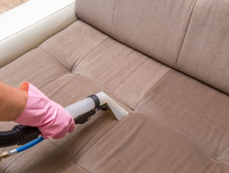 Parramatta cleaner extracting dirt off a brown sofa
